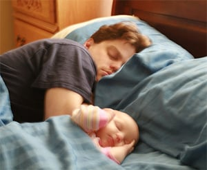 Kind naast snurkende papa