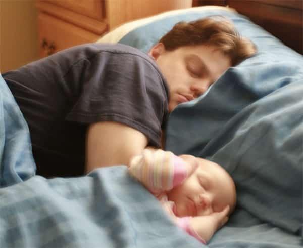 Vader snurkt in bed met een baby